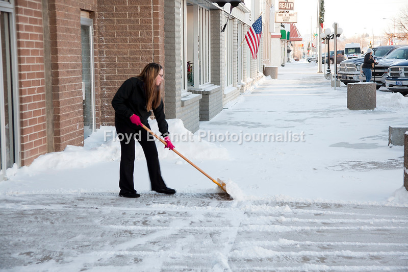 On a clear and cold day Cottonwood Cinema manager Erivka Ollinger shovels snow from in front of the cinema giving movie goers a clear path to the movies Wednesday. A warm place to wait out Havres sub below weather.