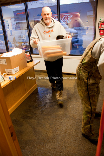 Excutive Vice President Gerry Veis clears his office at Bear Paw Credit Union as Chris Andrson vaccumes up water from a water pipe break that flooded the bank. The break happened outside the bank pushing the water under the door flooding the bank early Tuesday morning.