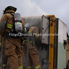 "Havre Daily News/Floyd Brandt<br /> <br /> Smoke poured out of a trailer parked at the Havre Fire Department where Firefighter Chris Cox enters the Confined Space Training trailer Monday Austin Shupe waits and watches for his turn at finding his way through the small space. The traing helps the firefighters prepare themselves for entering a fire that may be very confining and dangerous. Assisant Fire Chief Kelly Jones said that it gives his firefighters a chance to get use to their equipment and gear in small spaces and to look out for hazards. For Chris Cox, ""It was tight and you can't see anything but it was a lot of fun,"" he said."