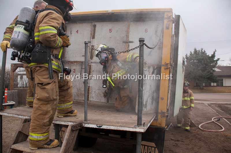 "Havre Daily News/Floyd Brandt<br /> <br /> Smoke poured out of a trailer parked at the Havre Fire Department where Firefighter Chris Cox waits and watches Austin Shupe exit from the Confined Space Training trailer Monday. The traing helps the firefighters prepare themselves for entering a fire that may be very confining and dangerous. Assisant Fire Chief Kelly Jones said that it gives his firefighters a chance to get use to their equipment and gear in small spaces and to look out for hazards. For Chris Cox, ""It was tight and you can't see anything but it was a lot of fun,"" he said."