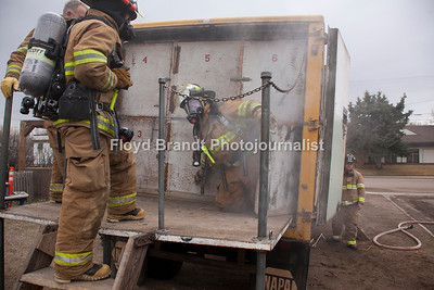 "Havre Daily News/Floyd Brandt  Smoke poured out of a trailer parked at the Havre Fire Department where Firefighter Chris Cox waits and watches Austin Shupe exit from the Confined Space Training trailer Monday. The traing helps the firefighters prepare themselves for entering a fire that may be very confining and dangerous. Assisant Fire Chief Kelly Jones said that it gives his firefighters a chance to get use to their equipment and gear in small spaces and to look out for hazards. For Chris Cox, ""It was tight and you can't see anything but it was a lot of fun,"" he said."