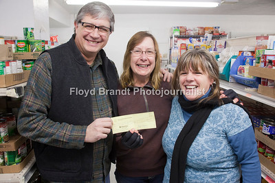 "The 5th Avenue Christian Church Miniater Frank Donato (left) and Adminstrative Assistant Carrie Linie (right) hands a donation from the church to Lorna Bjerga of the Havre Food Bank for the condtruction of a walk-in freezer at the Havre Food Bank Wednesday, Miniater Donato said ""the funds are from our Christmas Eve offering, that people are only asked to give if they can.""the donation was in the amount of $740.00 dollars."