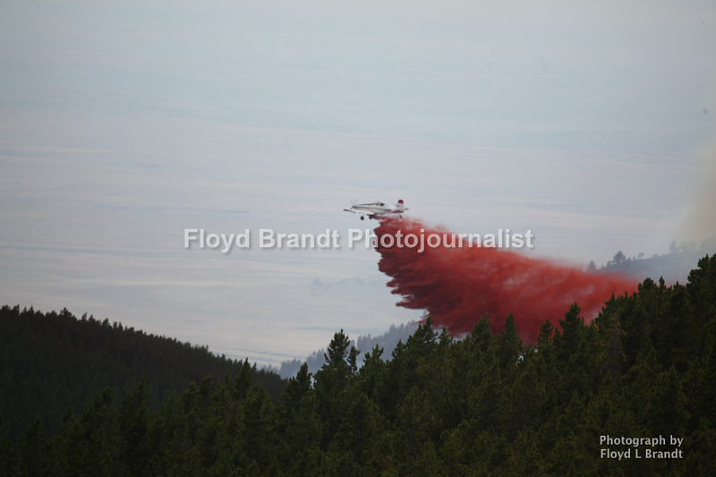 Havre Daily News / Floyd Brandt<br /> <br /> With the change in wind direction the fire back track over already burned area between the towns of Landusky and Zortman finding some new fuel in a bowl deep inside the Little Rockies giving the crew a hand to construct fire breaks with the battle going to air power Sunday. Airplanes carrying fire retardant drop it along the ridge of the mountain slowing the fire.
