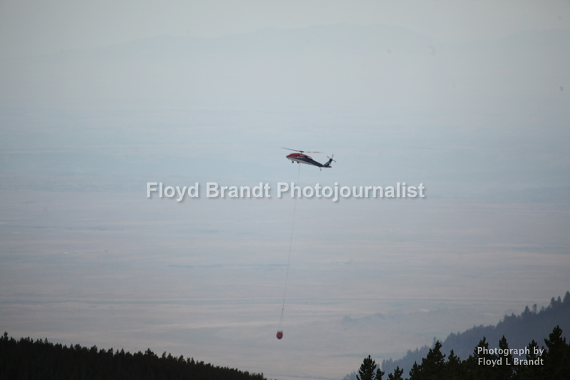 Havre Daily News / Floyd Brandt<br /> <br /> With the change in wind direction the fire back track over already burned area between the towns of Landusky and Zortman finding some new fuel in a bowl deep inside the Little Rockies giving the crew a chance to construct fire breaks with the battle going to air power Sunday. A Helicopter carries water to be dumped not the fire on the other side of the ridge.