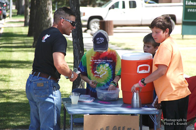 Havre Daily News / Floyd Brandt  Russell Friend President of Bull Riders Canada stops to buy a cool glass of lemon aid on a hot day from three boys Bryan Holt (left), Kasey Schafer and Soren Antonich at 4th street and 3rd avenue in Havre. Friend here for the bull riding at The Great Northern Fair in Hill County Saturday