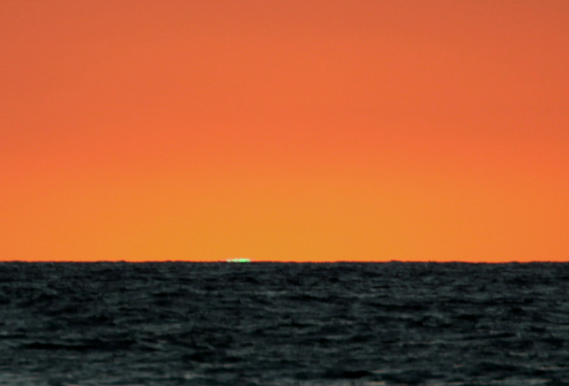 As the sun drops below the horizon it momentarily appears to be green.