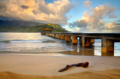 The Hanalei Pier is a great place to fish early in the morning, but I found nobody here for a few minutes just after sunrise. Within minutes, the fishermen appeared. I liked the light on the mountains in the background, which only occurs like this near the winter solstice.   I waited for that log to wash ashore and add a little extra interest up front.  Then I included a bit of the dry sand in the bottom of the frame to contrast with the wetter sand where the wave just washed ashore.  I also made sure that the lens was high enough to see a glimpse of the waves above the top of the pier on the right side.  Sometimes you have to think like a painter to improve the image.