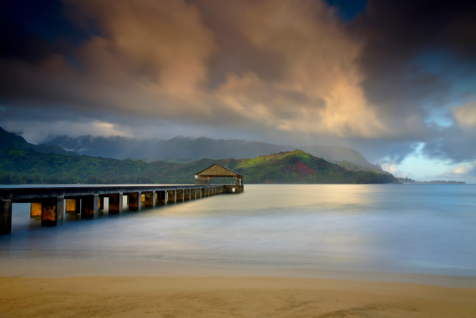 """The Hanalei Pier points directly towards the mountains often referred to as """"Bali Hai.""""   It refers to a song written by Richard Rodgers and Oscar Hammerstein II from the musical South Pacific. This area resembles the island of Tioman, which is the original Bali Hai.   With the sun rising behind the camera, openings in the clouds allowed the light to filter into the clouds and illuminate the mountains on the opposite side of Hanalei Bay.  Within 10 minutes the rain came in and this low warm light was gone for the day, replaced later by the bright light of mid-day.   I used a long exposure to show the motion in the clouds.  Also, the long exposure time smoothed out the water and simplified the image.  That enhanced the effect of light hitting the posts of the pier."""