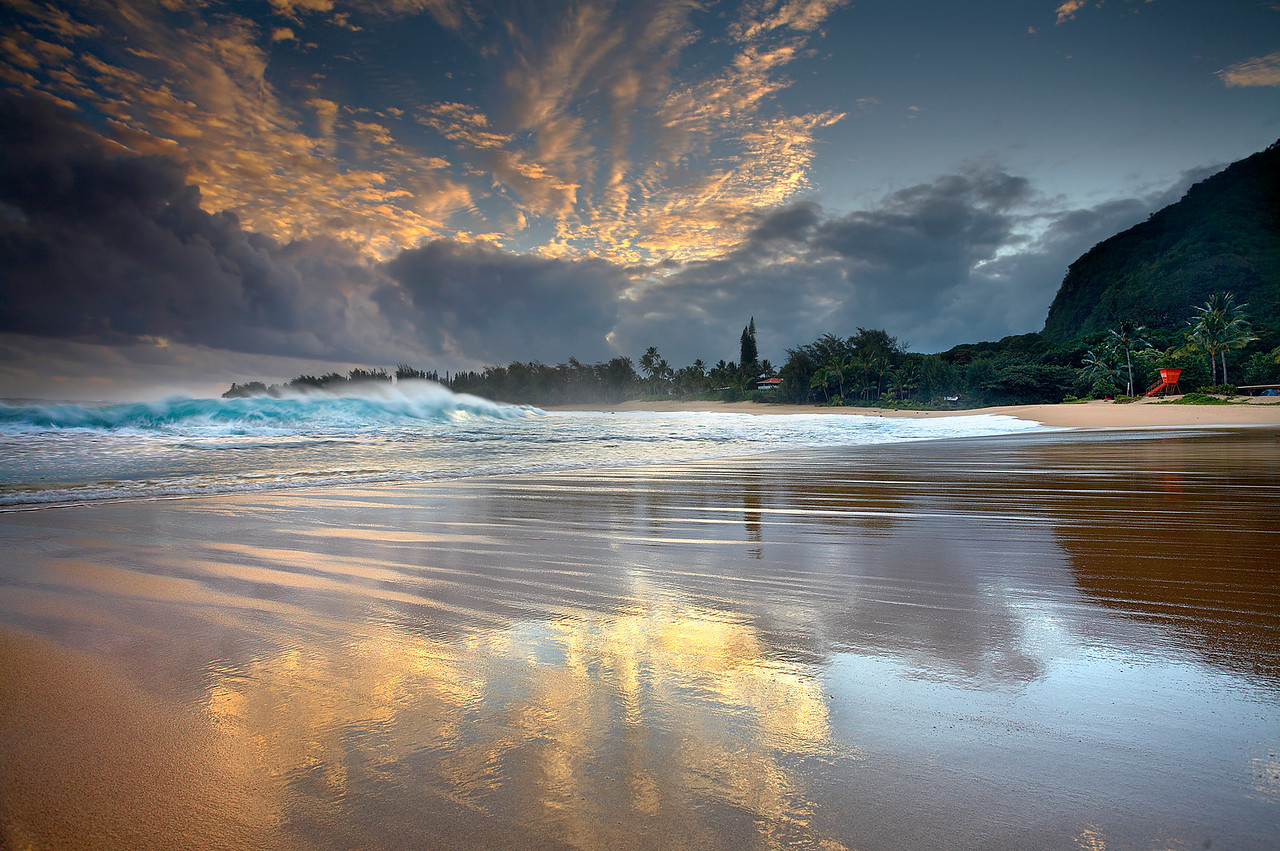 Originally, I came to this beach on the north shore of Kauai to make some images of the large waves there.  While I was concentrating on the motion of the water, I noticed how the sand turned reflective for just a few seconds between waves.  So I moved in closer to get a better view of the sand with the fast moving waves and well-lit sky in the background.  I had to choose smaller well-formed waves, as the larger ones obscured the trees in the background.   It took several attempts to capture a wave breaking while the sand was reflective and full of detail.  Usually the sand dried up before the next wave hit, but my patience paid off.