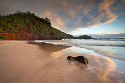 This beach is about 3 miles south of Hana, Maui.  The side closest to the red cliff has a bit of red sand, with a little red mixed into the coral based sand on the rest of the beach.  I walked up and down this beach before sunrise several times before spotting the symmetry between the cloud and the reflection in the periodically wet sand.  Then I waited for a while until the sand was wet again.  Two minutes later the light was bright and harsh and the show was over.  I believe that Ophah Winfrey owns this hill and the land behind it and to the right.  You can barely make out a striking sea arch on the right side.  It can not be accessed without crossing the land, at least from this side.