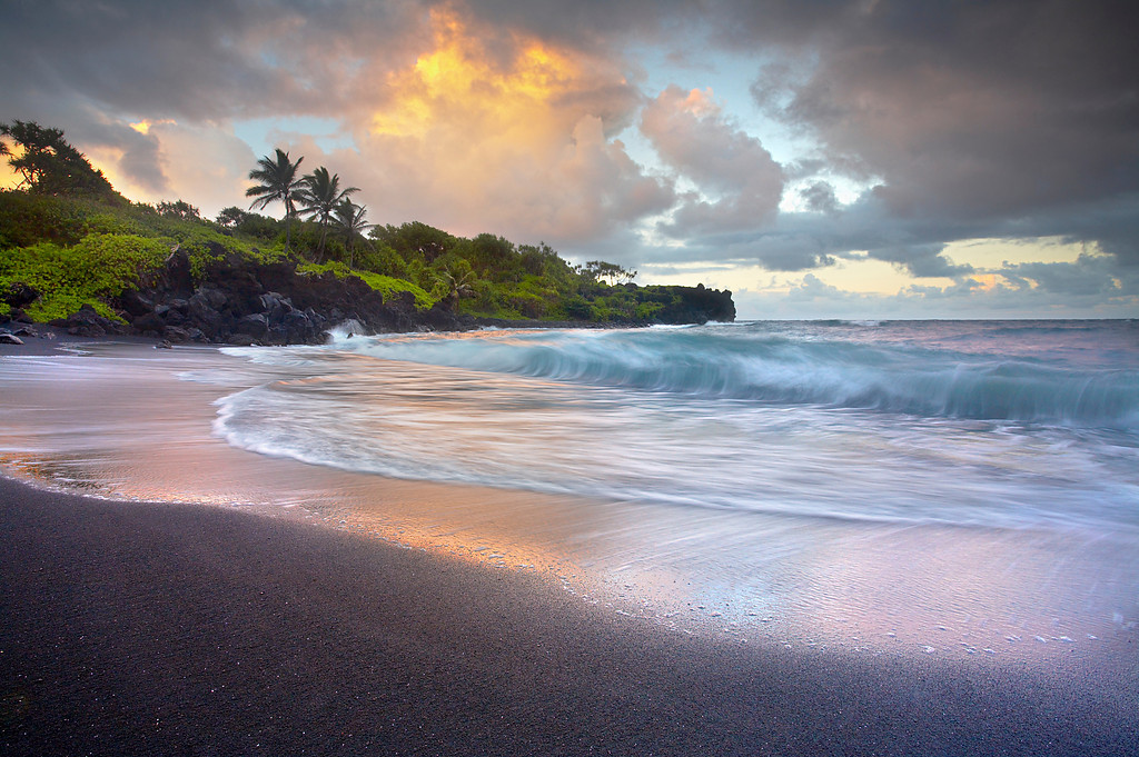 Waianapanapa means, 'glistening waters' and they are not kidding!   There are many ways to photograph this black sand beach near Hana, Maui.  But it takes a while to see the opportunities.  In this moment, the sand was briefly wet and reflected the last glowing light from the clouds above.  It took a while for a wave to break just when the sand was glowing.  I tried for 5 minutes before the timing was right.  A few minutes later the light was gone for the day.