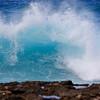 Waves crashing with blurry rocks in the foreground