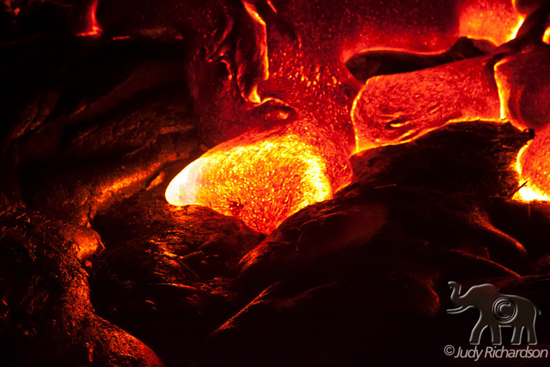 Hot molten lava flowing slowly from break-out points from Kilauea and Pu`u `Ō `ō vent. Pahoehoe lava moves forwards in tongues or lobes and is characterized by a glassy, smooth skin.