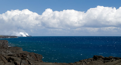 Whitecaps and clouds along Chain of Craters Road.  Steam and gas plumes from active lava flows entering the ocean are seen in the distance.