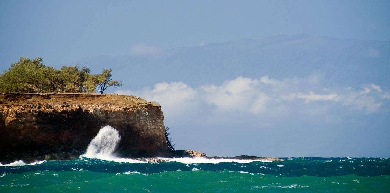 Crashing surf seen from near Holana Bay, with Maui's Haleakala Volcano and observatories visible in the distance.