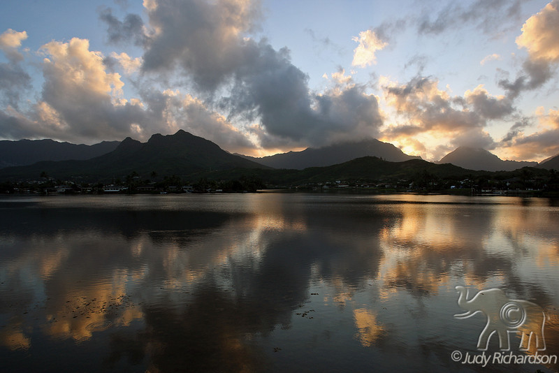 Spectacular sunset over Ko'olau Mountains and Mt. Olomana as clouds reflect in Enchanted Lake
