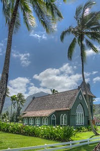 According to Bali Hai Realty, the picturesque Waiʻoli Huiʻia Church in Hanalei, located alongside the main road just past Hanalei town, is the most Photographed Building In Hanalei.  Built in 1912, the green, spired church was designed in the American Gothic style with a Roman Doric.  Filling the front gable of Waiʻoli Huiʻia Church is a large stained glass window with a pointed arch. The bell tower holds the bell that was formerly in the old Waiʻoli Belfry where it had summoned the Waiʻoli congregation since in 1843. Just behind Waiʻoli Huiʻia Church is the original Waiʻoli Church which is now called Waiʻoli Mission Hall. It was built in 1841 along with the Belfry which is also still standing having been fully restored. Farther back on the property behind a grove of trees is the historic Waiʻoli Mission House built in the 1830s.
