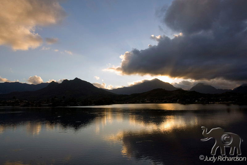 Last remaining rays of sun with Ko'olau mountains and Mt. Olomana reflecting in Enchanted Lake