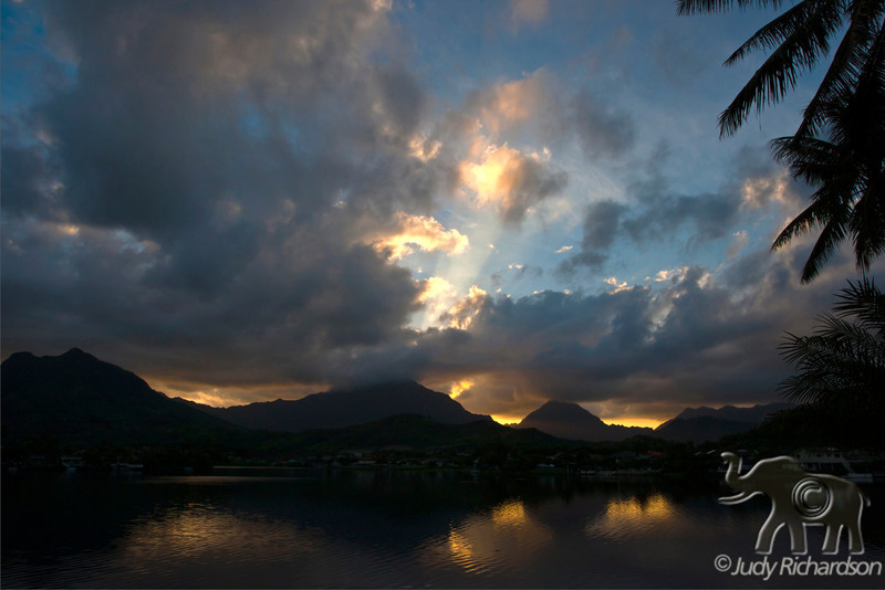 Stormy skies forming with beautiful sunset visible over the Ko'olau Mountains and Enchanted Lake in Kailua, O'ahu, Hawai'i.