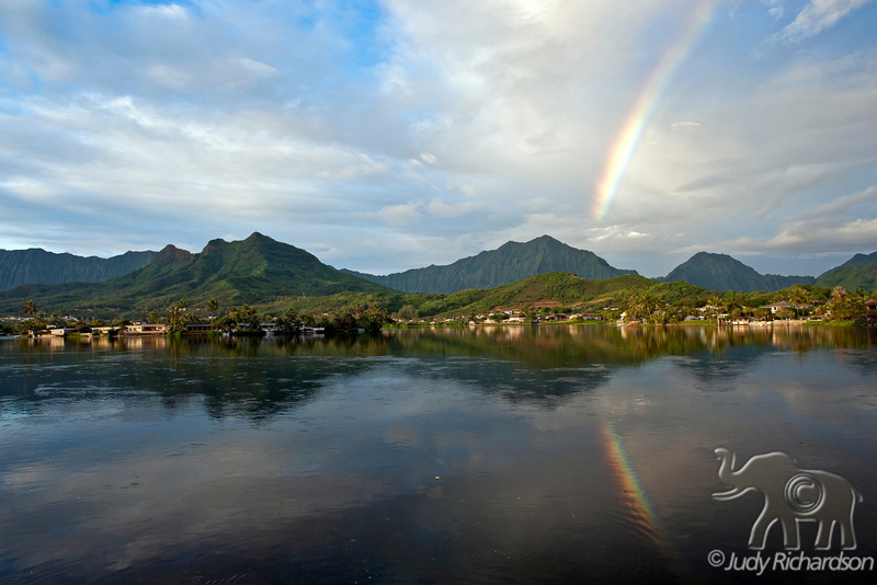 Rainbow reflecting in Enchanted Lake early in the morning over the Ko'olau Mountains and Enchanted Lake in Kailua, O'ahu, Hawai'i.
