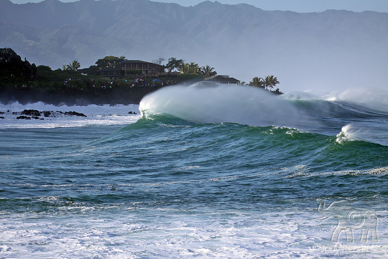 Scenic wave action in Waimea Bay with spectators on rocky bluff behind