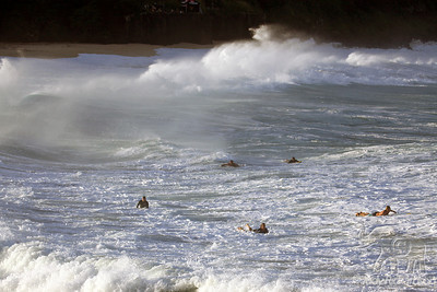 Surfers heading out through the heavy shore break to massive waves
