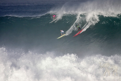 Three surfers on the face of a giant wave