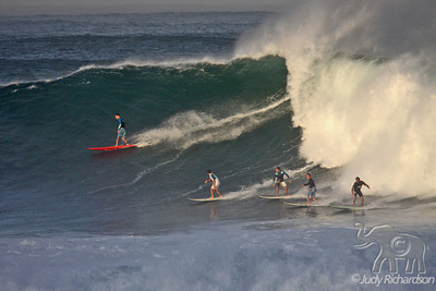 Five surfers catching a wave