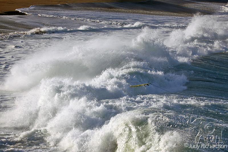 Surf board missing surfer in pounding shore break