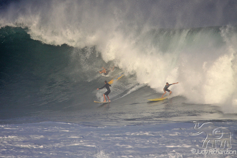 Surfer wipes out as two others surf on