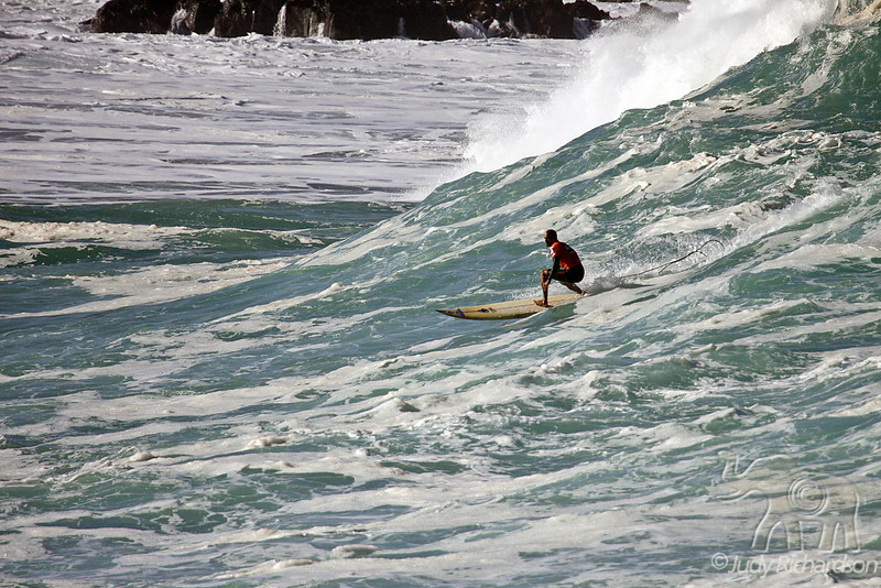 Surfing down the choppy, foaming wave face