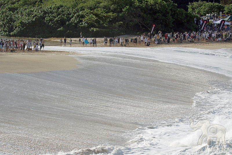 Surf spills over to where spectators are standing along the crest of Waimea Bay