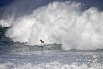 Giant splash behind surfer