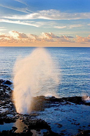 Spouting Horn, Kauai. This is a blow hole in a lava bench. When the waves crash in, water is forced up through the hole. It is unique to other such blowholes on the island because it is accompanied by a smaller hole that only has air forced through it, creating a moaning sound.