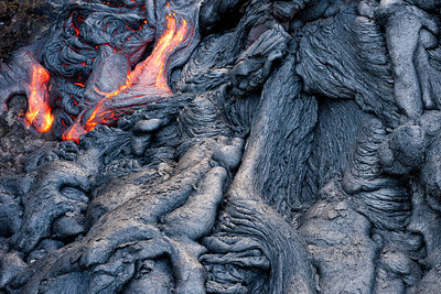 Molten lava streaming across solidified lava from Kilauea in Hawaii's Volcanoes National Park, on Hawaii's Big Island of Hawaii.