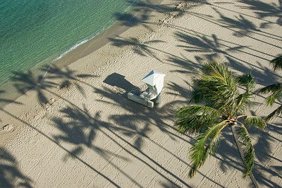 Palm tree shadows and lifeguard hut. Shot from above, palm tree shadows on the sand and a lifeguard hut keeps the beach safe early in the morning. Waikiki, Oahu, Hawaii.