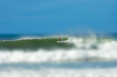 Surfing on a huge wave, blurred background and foreground makes it look like a miniature surfer.