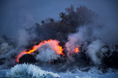 "Glowing lava entering the Pacific Ocean causing eruptions of steam as surf collides with molten rock from Hawaii""s Volcanoes National Park, Hawaii, Hawaii."