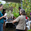 A West Hawaii Today reporter interviews a festival-goer who bought a native plant.