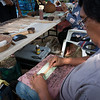 George Place demonstrates ohe kapala (bamboo pattern stamp) that he just made.
