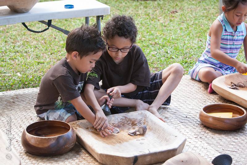 Haden Konanui teaches keiki how to pound taro the traditional way.