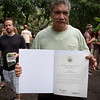 Uncle Keiki displays a certificate of recognition from the Hawai'i State House of Representatives for Kua O Ka La Public Charter School's contributions to Hawaiian culture, Hawaiian values, Hawaiian Lifestyle, and youth education, received on the day of the festival.