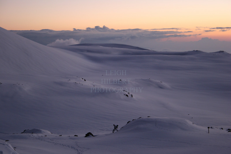 Just after sunset, looking for that last run of the day, a lone snowboarder treks across a moon-like volcanic landscape near between the two massive cindercones on Mauna Kea volcano, Island of Hawaii.<br /> <br /> ~ No chairlifts on this mountain!