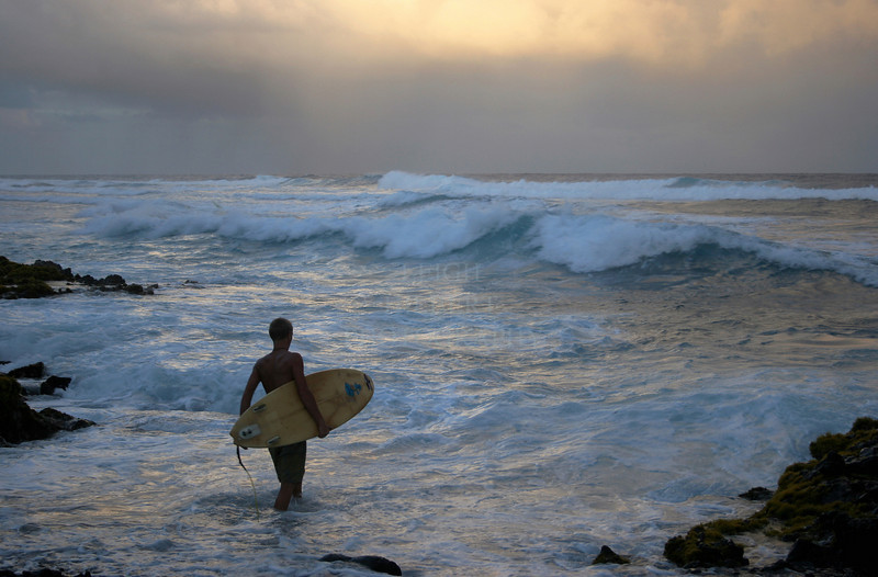 Surfer enters the sea for an end of the day surfing session, Island of Hawaii.<br /> <br /> Prints beautifully up to 30X40-inchs, but 'standard' print sizes work best, printing nicely up to 24X36-inches .