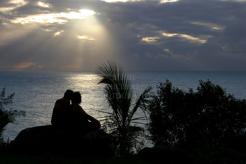 Lovers cuddle to watch the setting sun along the Napali coast on the Island of Kauai, Hawaii.