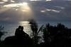 Lovers cuddle to watch the setting sun along the Napali coast on the Island of Kauai, Hawaii.