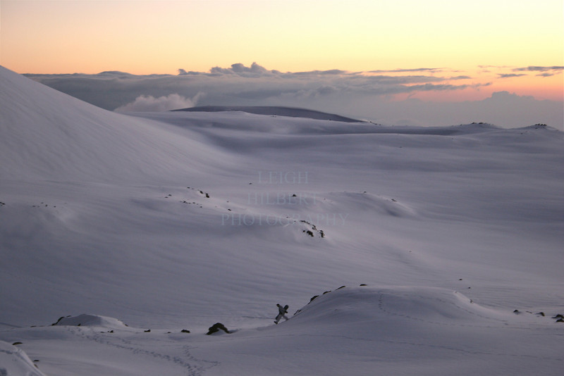 Just after sunset, looking for that last run of the day, a lone snowboarder trecks across a moon-like volcanic ladnscape near between the two massive cindercones on Mauna Kea volcano, Island of Hawaii.<br /> <br /> ~ No chairlifts on this mountain!