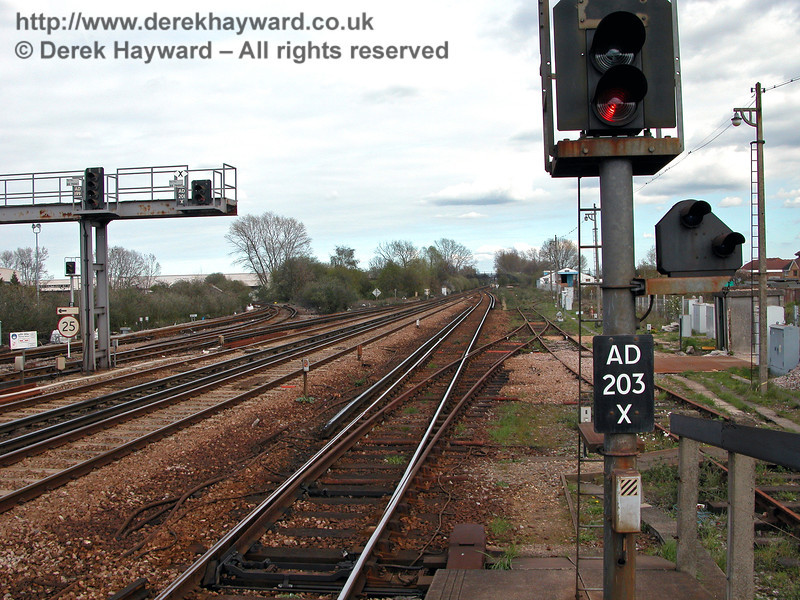 The reverse of the previous view, looking east from the end of Paddock Wood station.  The track layout has changed, but essentially Hawkhurst line trains departed from the bay on the right hand side of signal AD203X, and then used roughly the line of the disused siding before joining a track which led east parallel to the two track main line.  After about half a mile the branch line curved south away from the main line.  12.04.2004