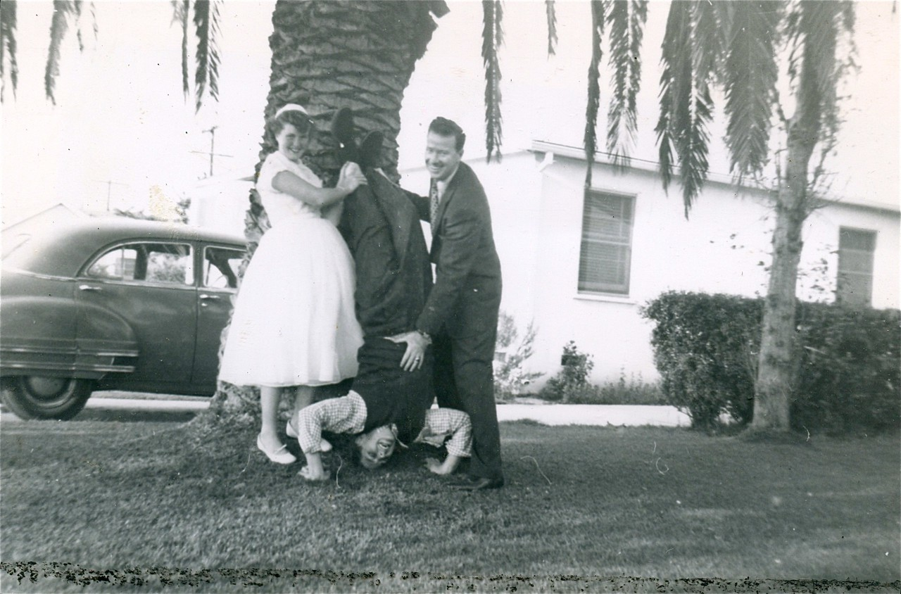 Carol Cotton and Bill Monahan holding Tom Cotton upside down at our home on Grevillea Ave., Hawthorne, California