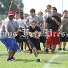 A camper at the Hays Rebel football camp takes the handoff during a drill in August. (Photo by MOSES LEOS III)